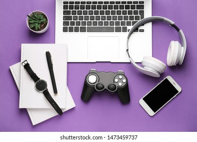 Laptop with joypad, mobile phone, headphones and stationery on color background