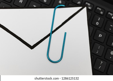laptop keyboard with envelope and clip symbol of email attachments, close-up shot at shallow depth of field