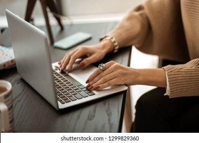 Laptop keyboard. Tidy woman in beige sweater with red manicure and having rarity ring on her point finger