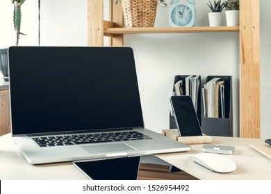 Laptop in a light room on working table with office supplies