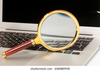 Laptop With Magnifying Glass lens close up.