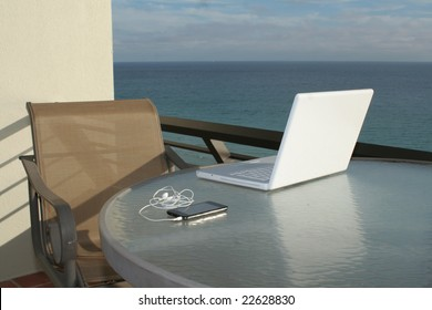 Laptop and media player refecting on glass with ocean view