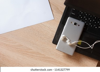 laptop and mobile phone with headphones on a wooden table