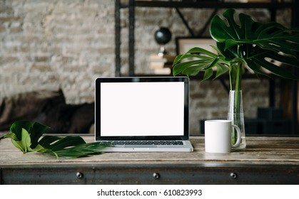 Laptop mock up on wooden table with cup of coffee or tea, monstera plant in vase. Working space in loft. Interior photo