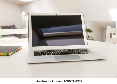 Laptop mock-up in bright apartment with flowers
