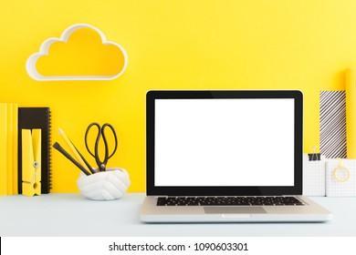 Laptop mockup on creative yellow desk.