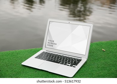Laptop Mockup on the green grass