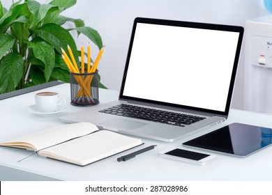 Laptop mockup with tablet computer, smartphone and notebook on the modern office desk. Consists of laptop, tablet computer, smartphone, notebook, cup of coffee. For design presentation or portfolio.