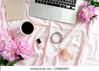 Laptop, mug of coffee, peonies, women cosmetics and accessories on pink linen