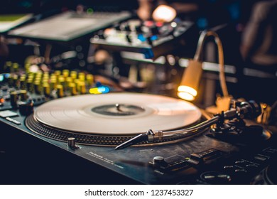 Laptop with music program on at the party in the club. Equipment for techno music. DJ playing techno music. Equipment set up with vynil.