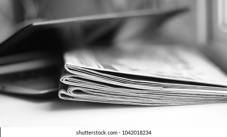 Laptop and newspapers. Computer and daily papers with fresh news. Folded journals and electronic device. Old fashioned and modern ways of communication and information. Actual data on paper or screen