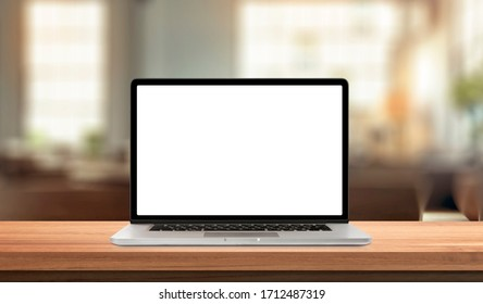 Laptop or notebook with blank screen on wood table in blurry background with house or office modern ,nature orange bokeh and sunlight in morning.