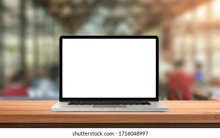 Laptop or notebook with blank screen on wood table in blurry background with coffee shop and nature green bokeh and sun light in morning. - Shutterstock ID 1716048997