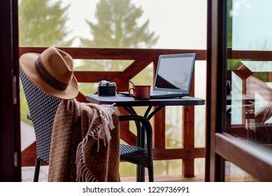 Laptop or notebook, camera, cup on the table. Concept of freelance or remote business, bloger, writer.