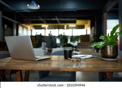 Laptop, notebook and eyeglasses sitting on a desk in a large open plan office space after working hours