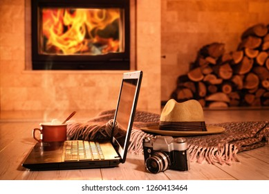 Laptop or notebook, hat,  camera, cup on the fireplace background. Concept of freelance or remote business, bloger, writer.