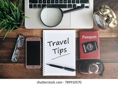 laptop, notebook, smartphone, passport, compass, magnifying glass and clock with TRAVEL TIPS word on wooden table. travel concept