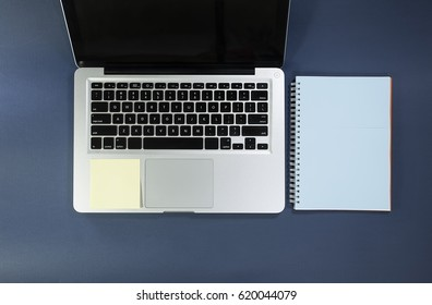 Laptop with notebook and sticky note