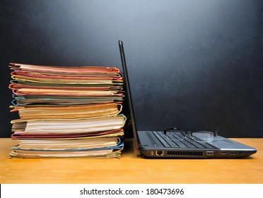 Laptop and office files on wooden table in front of black wall