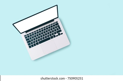 Laptop and office supplies on white table