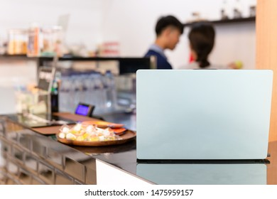Laptop on counter coffee bar with barista working in bur background.