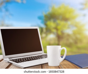 Laptop on desk outdoors in garden, home office concept.