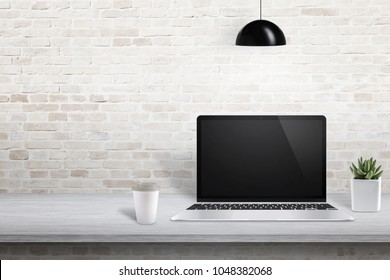 Laptop on office desk with free space on left side for text, picture frame or product presentation.