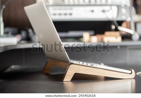 The laptop is on the table. Computer on a wooden stand.