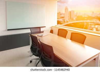 Laptop on table in empty corporate conference room with cityscape view on background. selected focus on laptop.