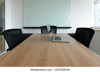 Laptop on table in empty corporate conference room