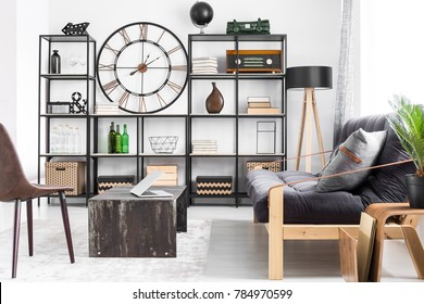 Laptop on table and grey pillow on couch in man's living room interior design with metal clock on the wall between shelves