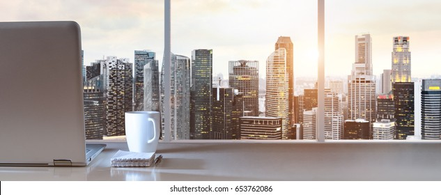 Laptop on table in office with panoramic sunset view of modern downtown skyscrapers at business district