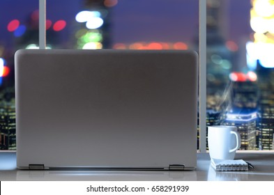Laptop on table in office with panoramic night view of modern downtown skyscrapers at business district
