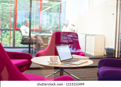 laptop on a table with pink and purple chairs and office with two men working in the background, real life small business