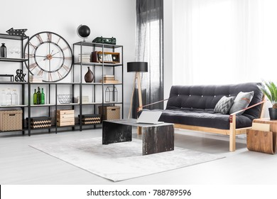 Laptop on table and wooden sofa in bright living room interior with industrial clock and bottles on a shelf