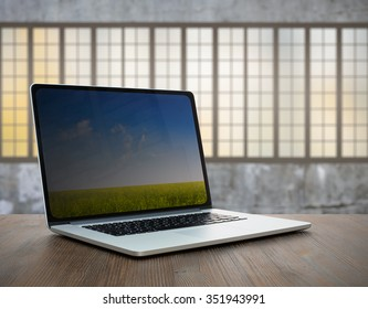 laptop on vintage wooden table in old room with big windows