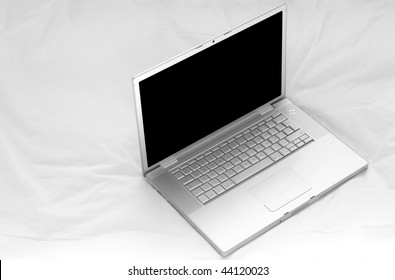 A laptop on a white duvet