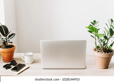 Laptop on wooden desktop with phone, notebook, coffee, glasses and plant in stylish modern room. Freelance concept. business workspace in home or office. stylish work place. working online