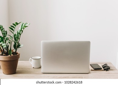 Laptop on wooden desktop with phone, notebook, coffee cup and plant in stylish modern room. Freelance concept. business workspace in home or office. stylish work place. working online