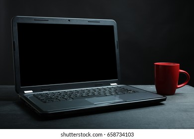 The laptop is on a wooden table on a black background. Concept blogging.