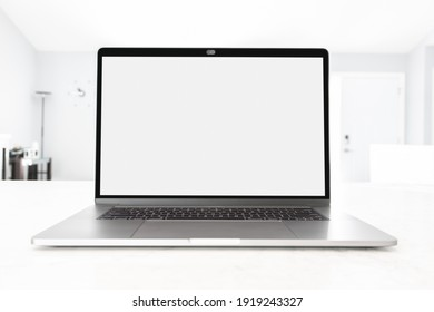 Laptop open with blank screen on a white table at workplace with blurred bright sunlight through the window, front view. Work from home concept with minimal modern home, depth of field.