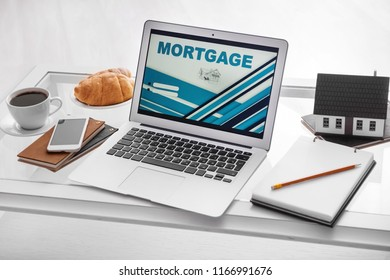 Laptop with open page for mortgage loan payment on table
