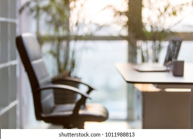The laptop is opened in modern office, Nobody in the chair.Blurred.