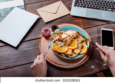 Laptop and pancakes with juice nd female hands. Healthy breakfast. Fresh homemade french crepes made with ffresh fruits on a vintage wooden board on the wooden table. Top view with honey, fruits and