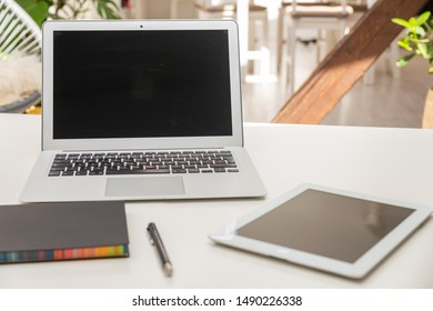 Laptop and PC tablet mock-up in bright apartment with flowers