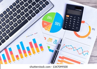 Laptop and pen with business charts, graphs, statistic and documents background for education and business concepts
