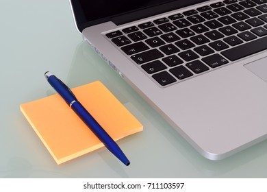 Laptop with pen and post it over crystal desktop