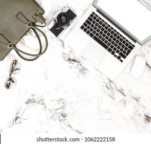 Laptop, phone, bag, vintage photo camera. Fashion flat lay for feminine website social media