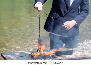 A laptop and a phone burned out on an office desk near the river. The male hand of a freelancer, manager or businessman holds the wire of the telephone receiver on fire. The concept of hated work or