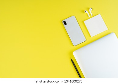 Laptop Phone Earphone Yellow Minimal Top Layout Flat Lay. Smartphone and Airpod on Freelance Business Workspace Background. Blank Corporate Workplace Inspiration Simple Concept Above Flatlay